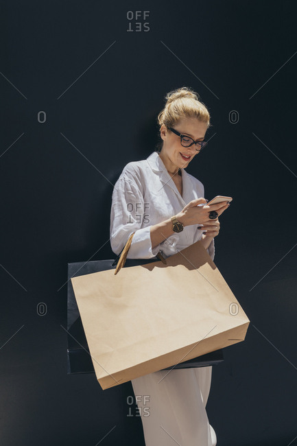 Portrait of beautiful smiling Caucasian woman holding shopping bags and typing on her cell phone.