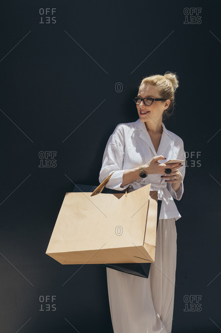 Portrait of beautiful smiling Caucasian woman holding shopping bags and a cell phone.