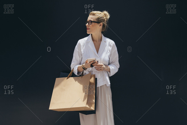 Portrait of pretty stylish Caucasian woman holding shopping bags and cell phone.