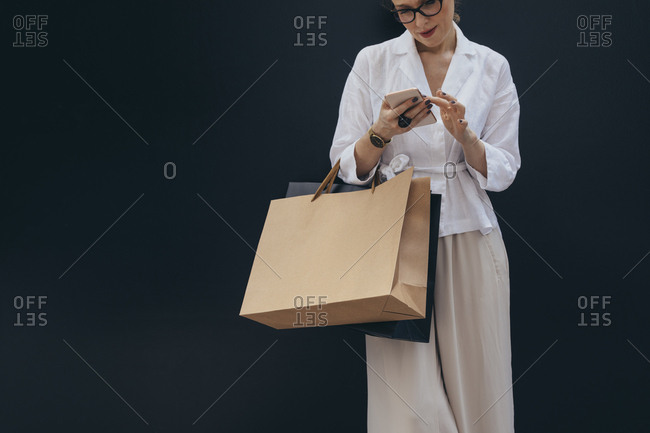 Pretty Caucasian woman holding shopping bags and typing on her cell phone isolated on black background.