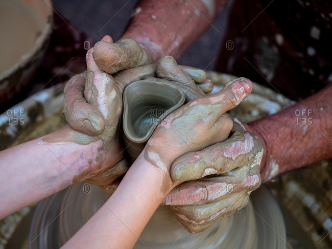 Potter helps a girl with his hands to create a clay pot on the lathe