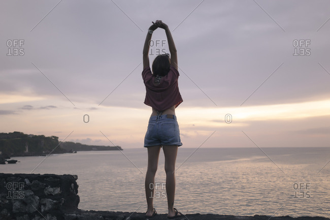 Rear view of woman with arms raised standing on retaining wall by sea against cloudy sky