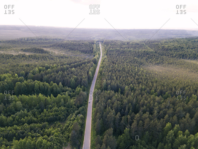 Aerial view of road amidst landscape against sky in forest