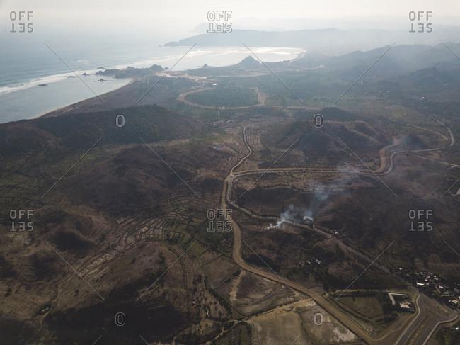 Aerial view of road in valley near ocean