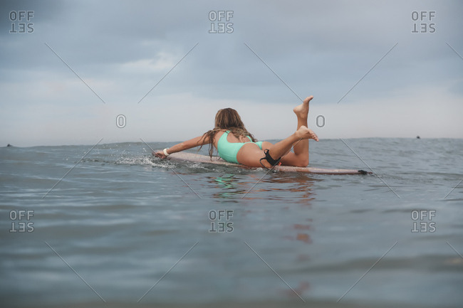 Woman lying on surfboard while swimming in sea