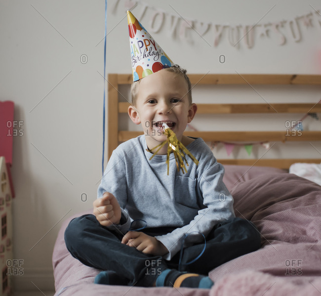 Portrait of happy boy playing with party horn blower while sitting on bed against wall at home