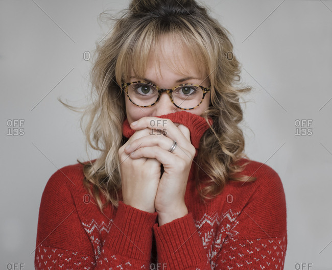 Portrait of woman wearing eyeglasses standing against gray background