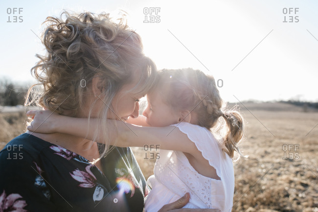 Mother and daughter in summer dresses laughing and smiling at sunset