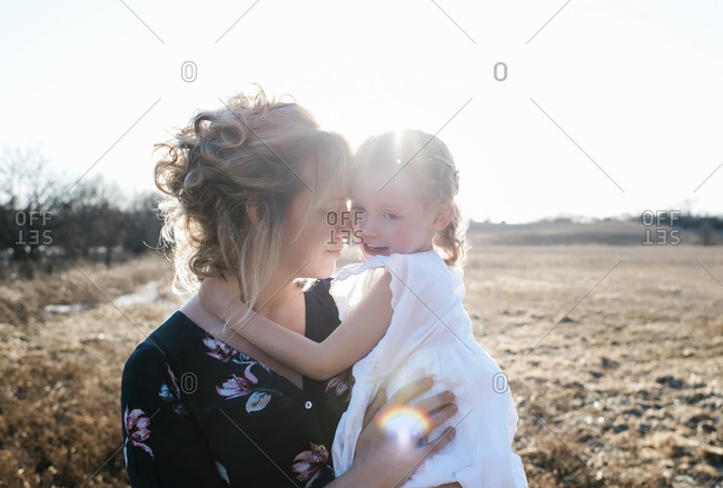 Mother and daughter hugging and smiling with the sunsetting in summer
