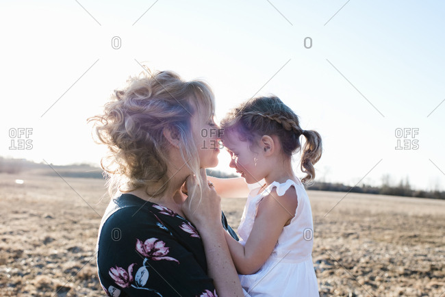 Mother holding daughter cuddling and smiling at sunset in summer