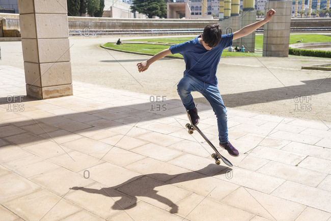 Boy performing stunt on skateboard in city