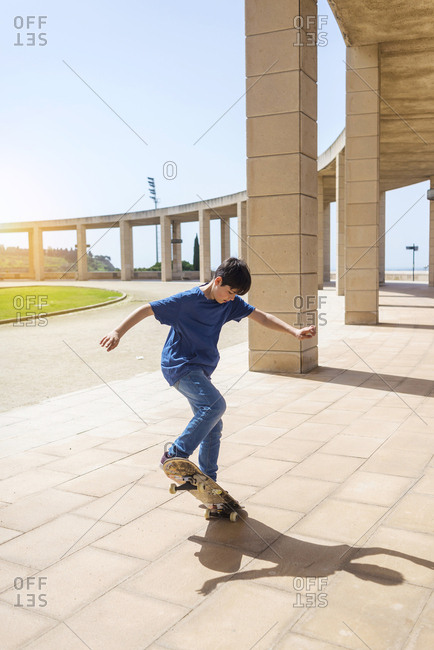 Full length of boy performing stunt on skateboard in city