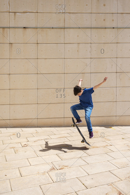 Boy performing stunt on skateboard against wall