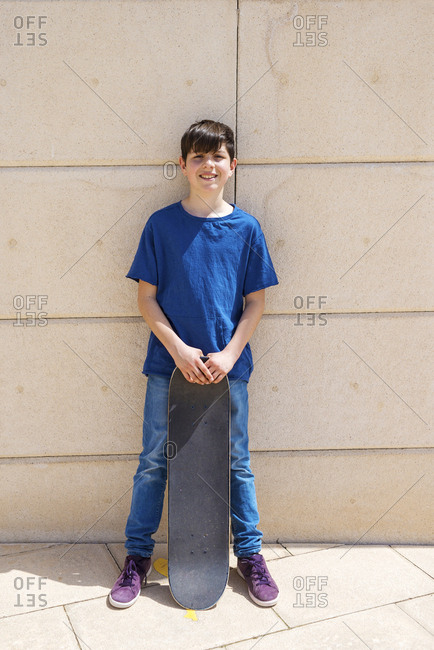 Full length portrait of boy with skateboard while standing against wall
