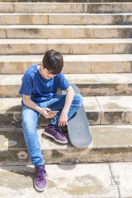 High angle view of boy using smart phone while sitting with skateboard on steps