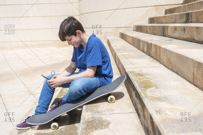 Full length of boy using smart phone while sitting with skateboard on staircase in city