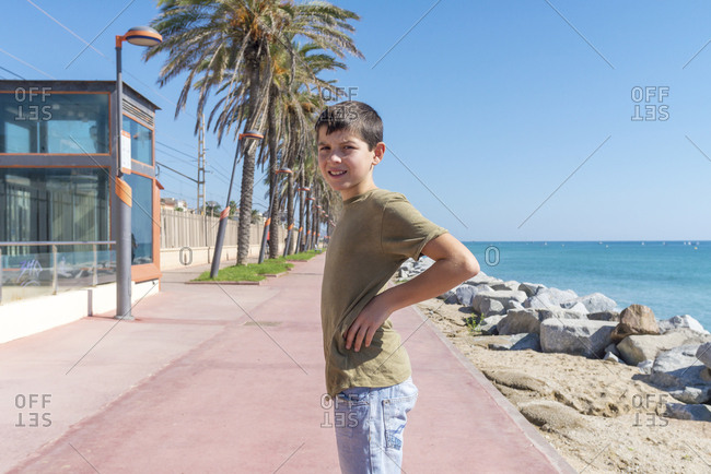 Front view of a young teen smiling while standing on a promenade