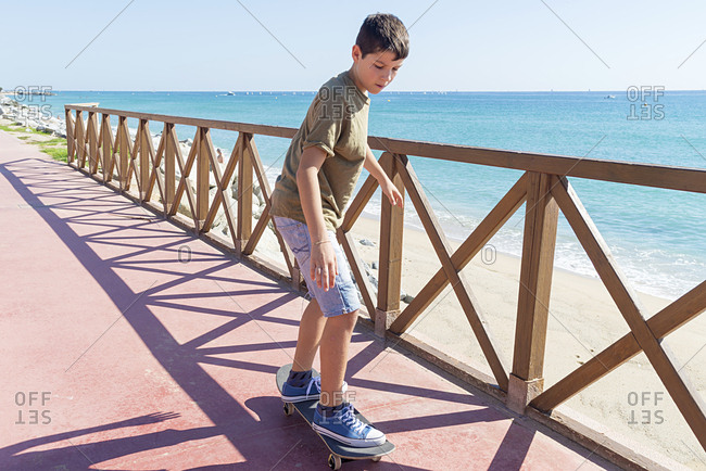 Front view of a young teen skateboarding on promenade in sunny day