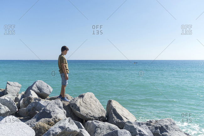 Side view of young boy standing on seashore while looking away