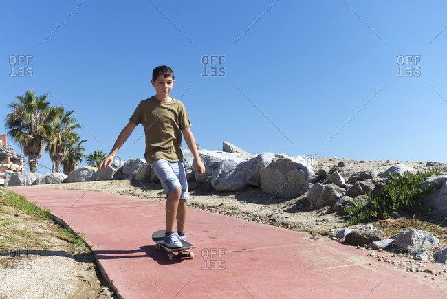 Front view of young boy skateboarding on promenade in sunny day