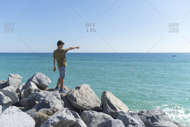 Side view of a young boy standing on seashore while pointing to horizon