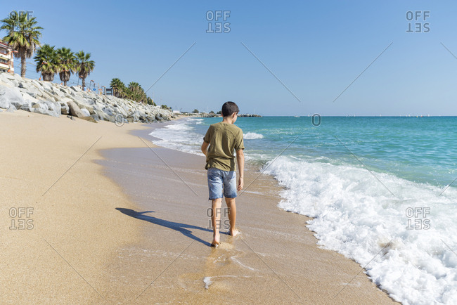 Rear view of young boy barefoot  walking on seashore in sunny day