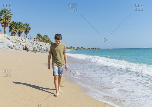 Front view of young boy walking on the beach while looking down