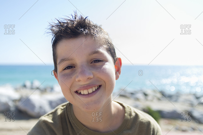 Close up portrait of young boy in a sunny day while smiling