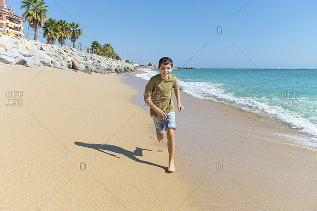 Front view of young boy barefoot running on beach while smiling