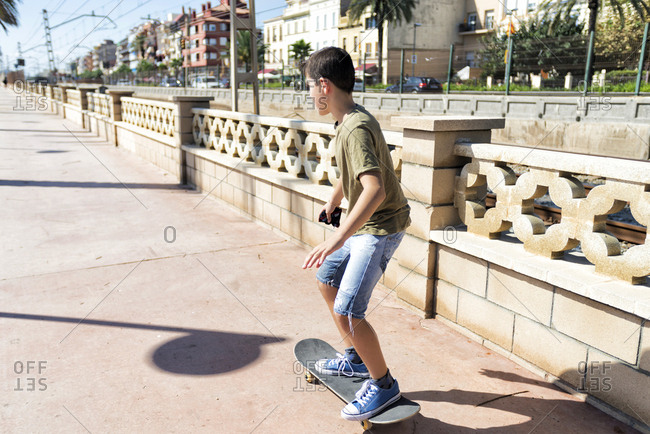 Rear view of young skater boy riding on promenade in a sunny day