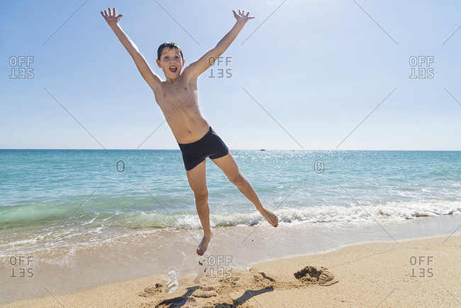 Front view of young boy jumping on beach while smiling in a sunny day