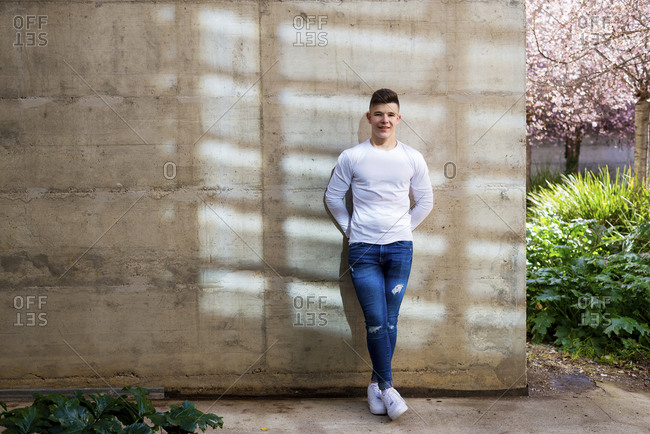 Front view young man leaning on a wall while looking camera