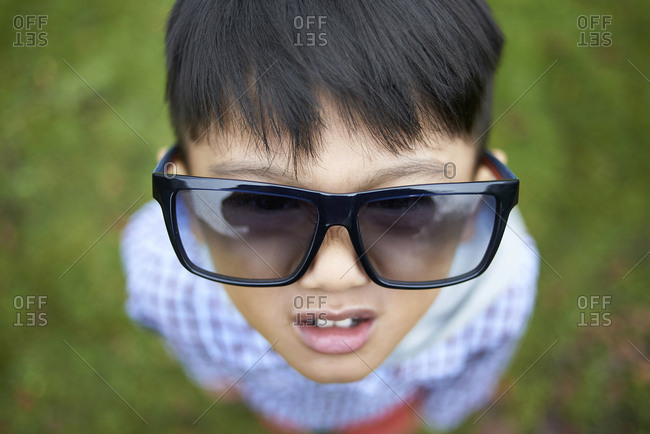 High angle view of boy wearing oversized black sunglasses while standing on field at park
