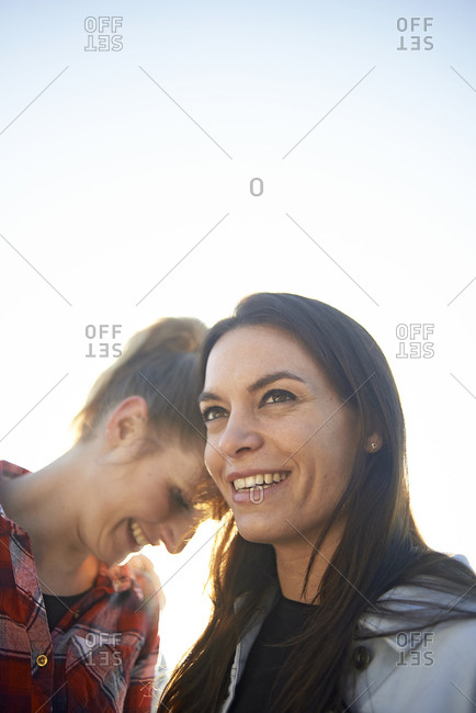 Happy lesbian couple looking away against clear sky during sunset