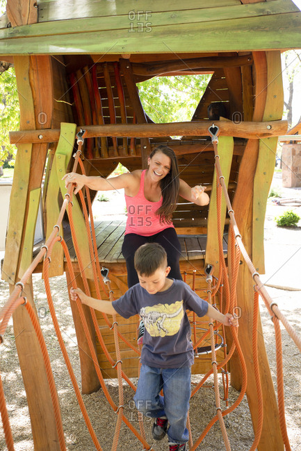 Happy mother and son playing on outdoor play equipment at playground