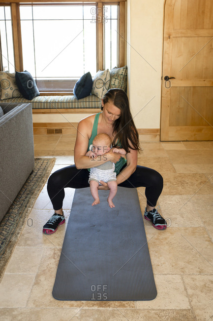 Mother carrying cute daughter while exercising at home