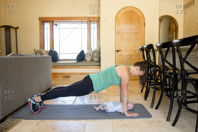 Side view of mother practicing push-ups with daughter on exercise mat at home