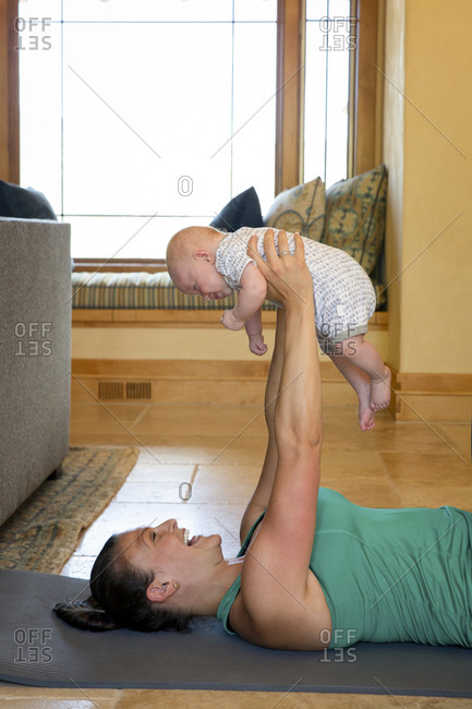 Side view of cheerful mother exercising with daughter on exercise mat at home