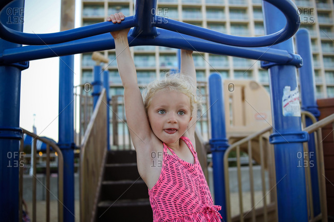 Girl doing monkey bars with tongue sticking out in pink dress