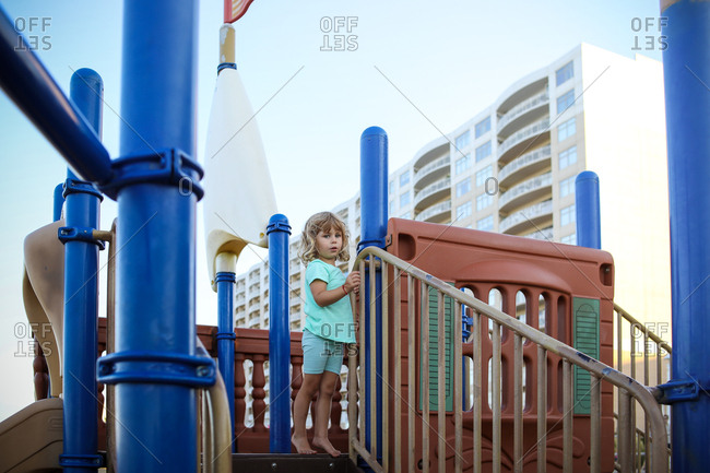 Little girl in blue on playground barefoot with blonde hair
