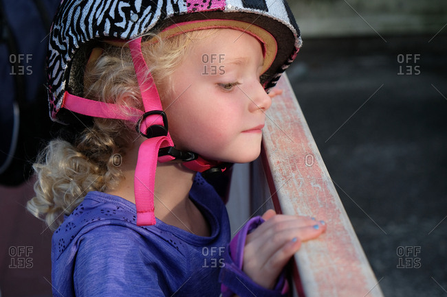 Close up of young girl wearing helmet peering over a railing