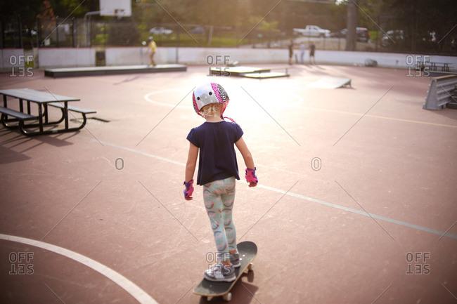 Backside view of girl at golden hour skateboarding at skatepark