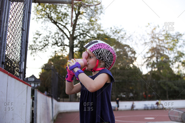 Young girl drinking water with wrist guards on at skatepark