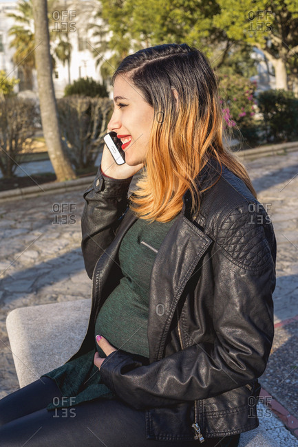 Portrait of a happy young pregnant woman talking on smartphone