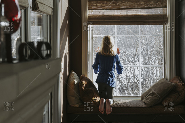 Rear view of girl looking through window while kneeling at home during winter