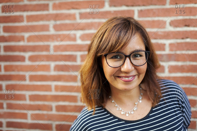 Close-up portrait of smiling woman wearing eyeglasses against brick wall
