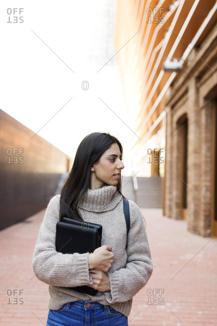 Young brunette woman walking outdoors  holding books