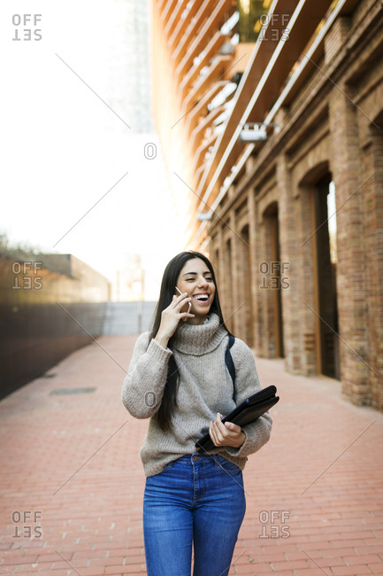 Student talking on smart phone while walking on city street