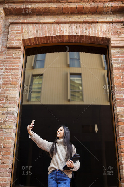 Full length of student woman using smartphone in front  window