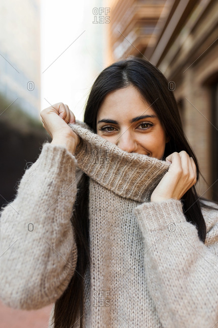 Portrait of young brunette woman wearing grey pullover